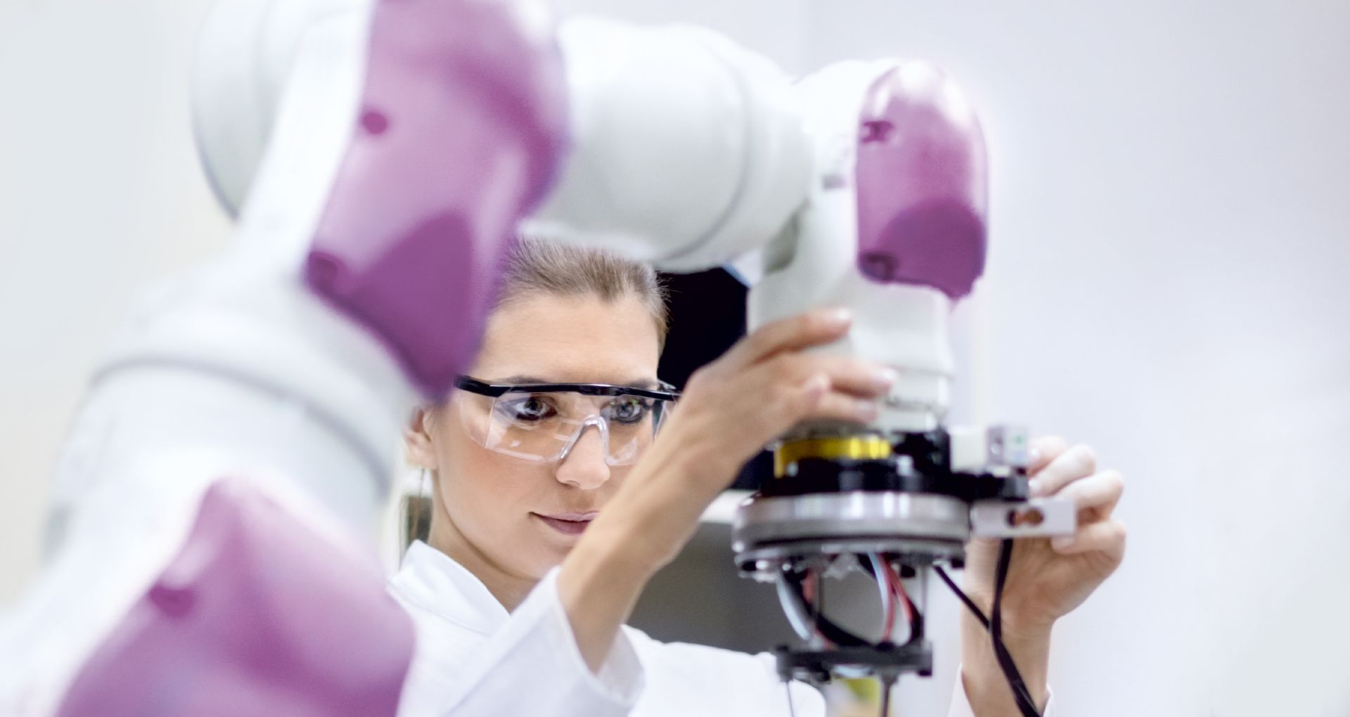 Mid adult female engineer working with robotic arm in research lab